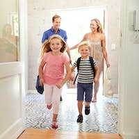 Family Returning Home From Shopping Trip Carrying Grocery Bags