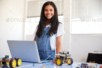 Portrait Of Female Student Building And Programing Robot Vehicle In School Computer Coding Class