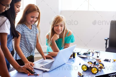 Three Female Students With Teacher Building Robot Vehicle In After School Computer Coding Class