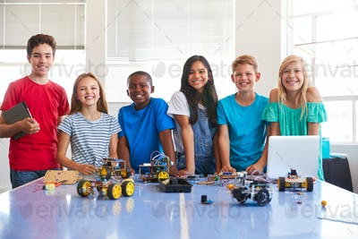 Portrait Of Male And Female Students Building Robot Vehicle In After School Computer Coding Class