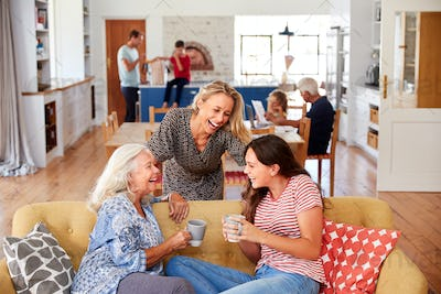 Mother With Adult Daughter And Teenage Granddaughter Relaxing On Sofa And Talking At Home
