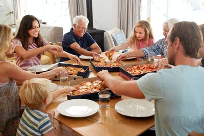 Multi Generation Family Sitting Around Table Eating Takeaway Pizza Together