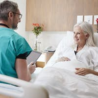 Surgeon With Digital Tablet Visiting And Talking With Mature Female Patient In Hospital Bed