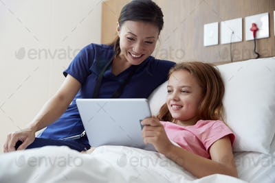 Female Nurse With Girl Lying In Hospital Bed Looking At Digital Tablet Together
