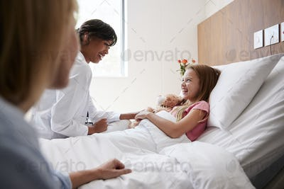 Female Doctor Visiting Mother And Daughter Lying In Bed In Hospital Ward