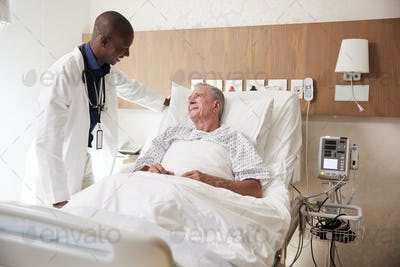 Doctor Visiting And Talking With Senior Male Patient In Hospital Bed