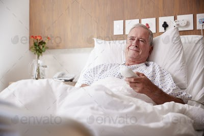 Male Senior Patient Lying In Hospital Bed Watching Television