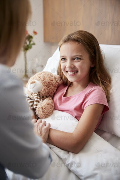 Mother Visiting Daughter Lying In Bed In Hospital Ward