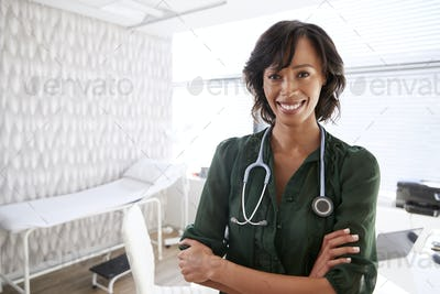 Portrait Of Smiling Female Doctor With Stethoscope Standing By Desk In Office