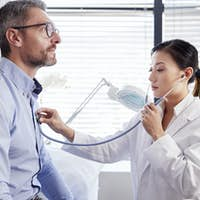 Mature Male Patient Having Medical Exam With Woman Doctor In Office