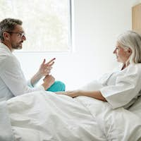 Doctor Wearing White Coat Visiting Mature Female Patient In Hospital Bed