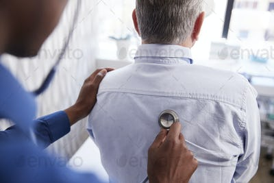 Senior Male Patient Having Medical Exam With Doctor In Office