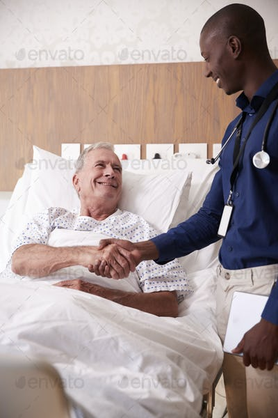 Doctor Shaking Hands With Senior Male Patient In Hospital Bed In Geriatric Unit