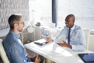 Mature Male Patient In Consultation With Doctor In Office