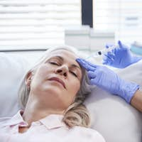 Beautician Giving Mature Female Patient Botox Injection In Forehead