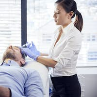 Female Beautician Giving Mature Male Patient Botox Injection In Forehead
