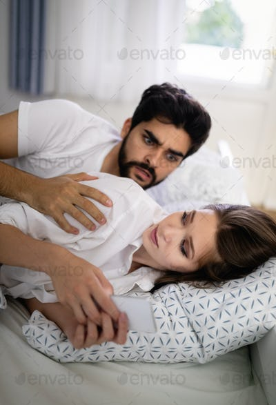 Confused young couple having an argument about mobile phone while lying in bed