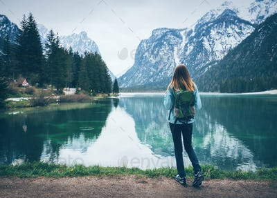 Young woman with backpack is standing on the coast of the lake