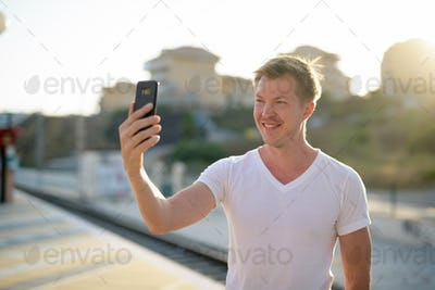 Happy man taking selfie with mobile phone at train station