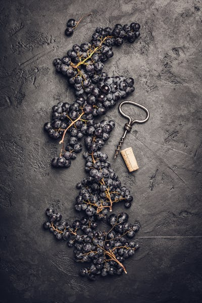 Fresh grape, cork and corkscrew on dark background