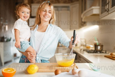Mother and daughter mixing ingredients for cake