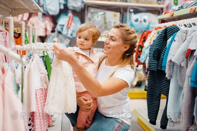 Mother with girl choosing clothes in kids store