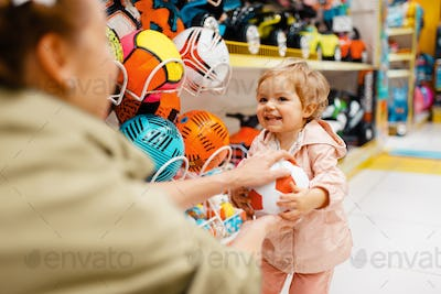Mother with daughter playing with ball in store