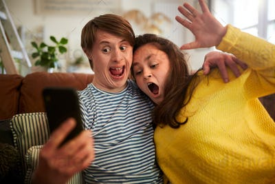 Young Downs Syndrome Couple Sitting On Sofa Using Mobile Phone To Take Selfie At Home
