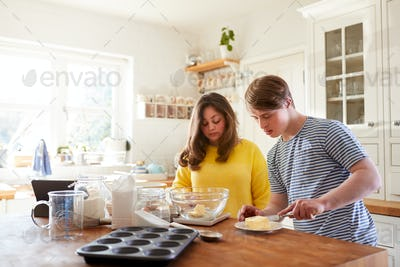 Young Downs Syndrome Couple Following Recipe On Digital Tablet To Bake Cake In Kitchen At Home