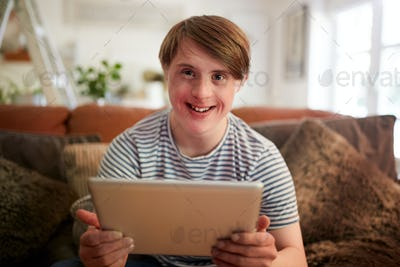 Portrait Of Young Downs Syndrome Man Sitting On Sofa Using Digital Tablet At Home