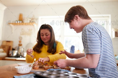 Young Downs Syndrome Couple Decorating Homemade Cupcakes With Icing In Kitchen At Home