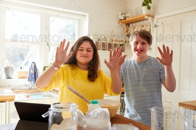 Portrait Of Downs Syndrome Couple Following Recipe On Digital Tablet To Bake Cake In Kitchen At Home