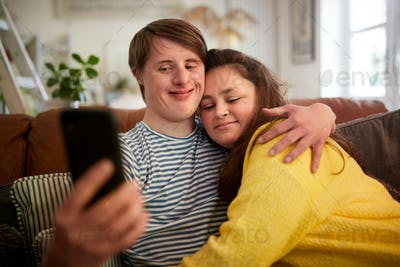 Loving Young Downs Syndrome Couple Sitting On Sofa Using Mobile Phone To Take Selfie At Home