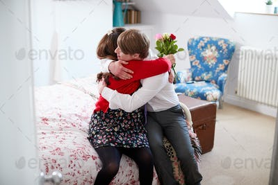 Loving Young Downs Syndrome Couple Sitting On Bed With Man Giving Woman Flowers