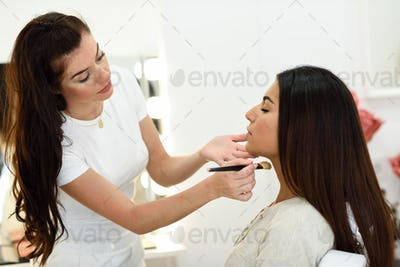 Makeup artist making up an African young woman in a beauty cente