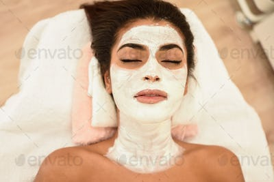 Young woman with moisturizer cream mask on her face