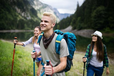 Smiling friends walking with backpacks. Adventure, travel, tourism, hike and people concept