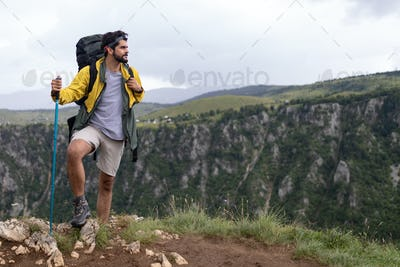 Young man traveling with backpack hiking in mountains