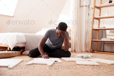 Frustrated Man In New Home Putting Together Self Assembly Furniture