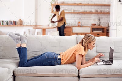 Woman Relaxing Lying On Sofa At Home Using Laptop Computer With Man In Kitchen Behind