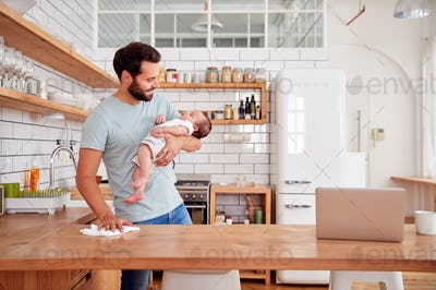 Multi-Tasking Father Holds Sleeping Baby Son And Cleans In Kitchen