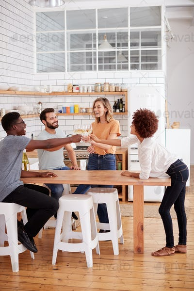 Two Couples Relaxing In Kitchen At Home Making A Toast With Glass Of Wine Together
