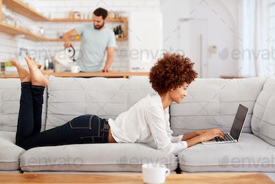 Woman Relaxing Lying On Sofa At Home Looking At Laptop