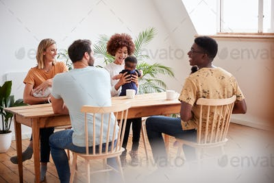 Two Families With Babies Meeting And Talking Around Table On Play Date At Home