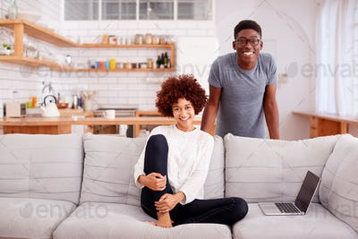 Portrait Of Couple Relaxing On Sofa At Home Looking At Laptop Together