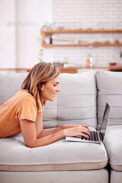 Woman Relaxing Lying On Sofa At Home Using Laptop Computer