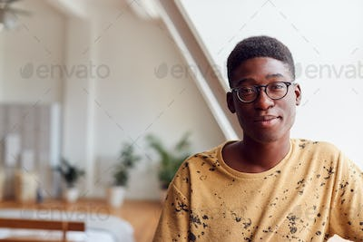 Portrait Of Smiling Young Man In Loft Apartment