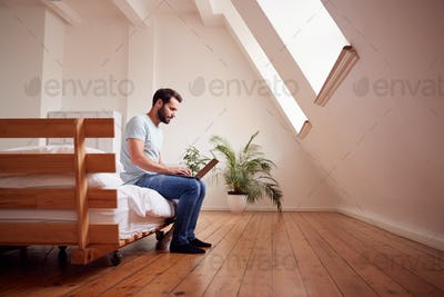 Young Man Sitting On Bed In Loft Apartment Working On Laptop