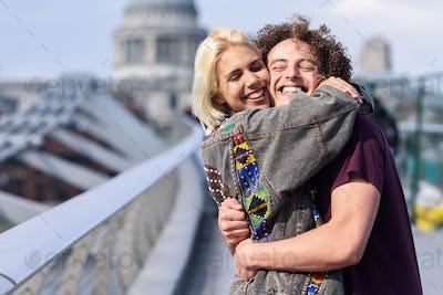 Happy couple hugging by Millennium bridge, River Thames, London.