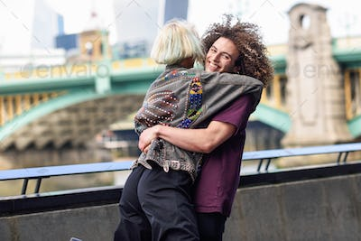 Happy couple hugging near the Southwark bridge over River Thames, London